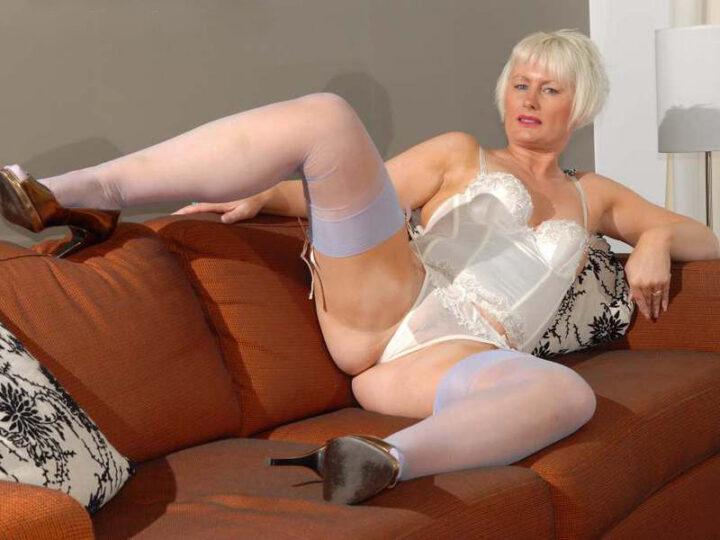 Зрелая женщина постарше лежит на диване широко раскинув ноги