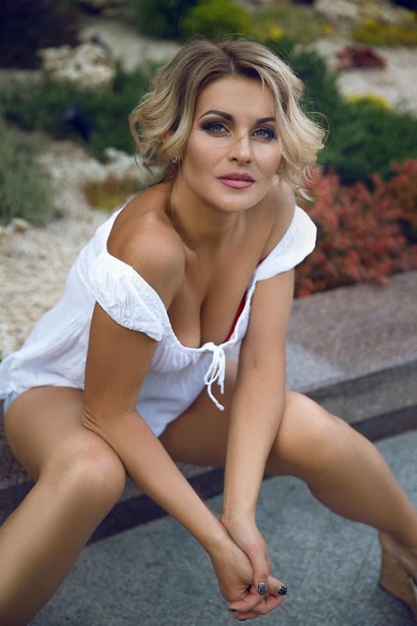 Сексапильная русская женщина в белом платьице с голубыми глазами