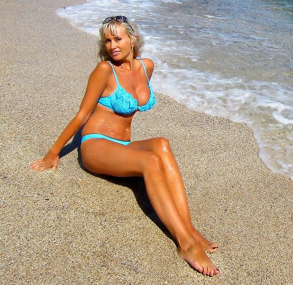 Загорелая русская женщина в купальнике на берегу моря