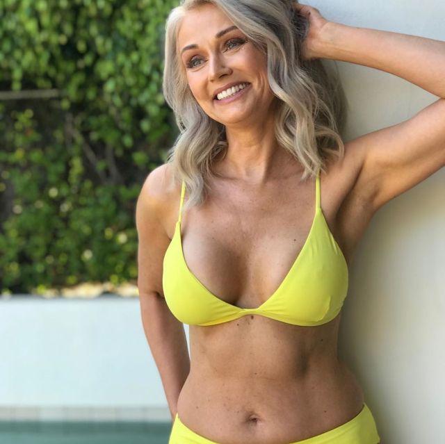 Улыбчивая и прекрасная зрелая женщина в желтом купальнике