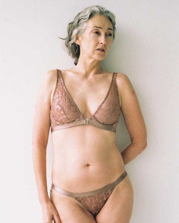 Зрелая женщина с азиатской внешностью в одном нижнем белье