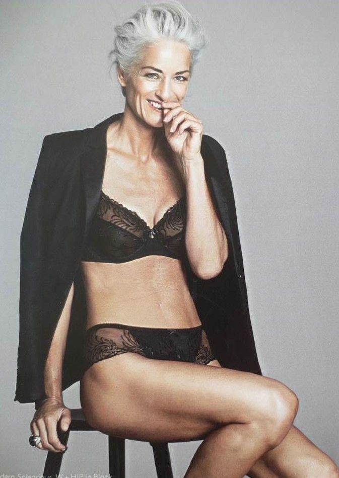 Привлекательная зрелая женщина за 50 в черном белье и накинутом пиджаке