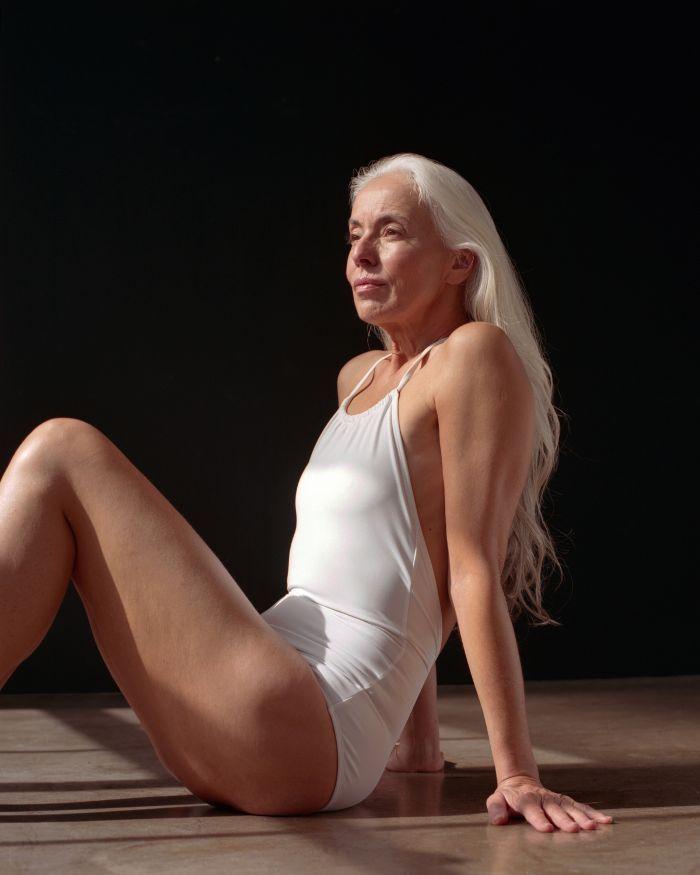 Красивая седоволосая зрелая женщина позирует в купальнике