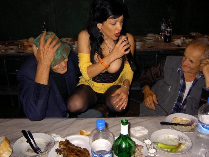 Пьяная певца с сиськами навыкат сидит на корточках между двух мужиков