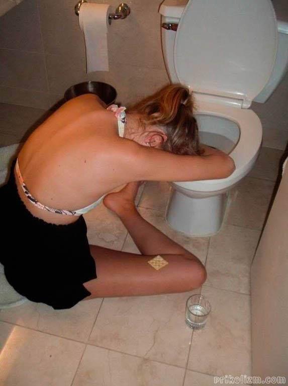 Пьяная девушка сидит на полу возле унитаза с печенькой на коленке