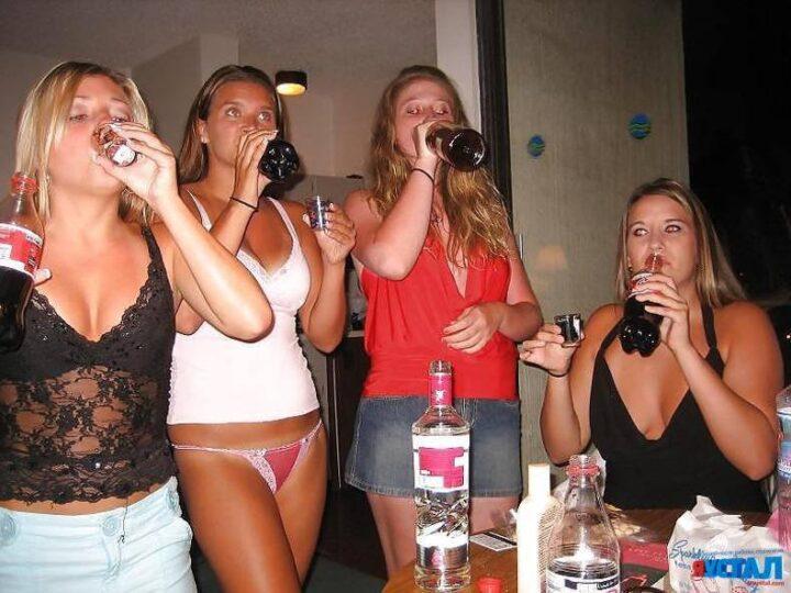 Пьяная загорелая девушка пьет, стоя в майке и мини трусиках