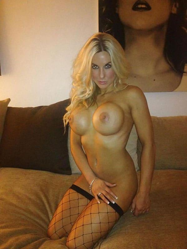 Блондинка с большими силиконовыми сиськами в чулках с соблазнительным взглядом