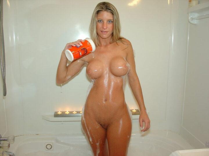 Блондинка в ванной поливает себя водой из стакана