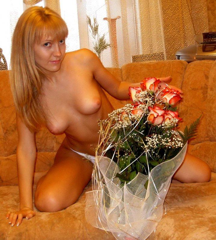 Красотка жена с букетом роз без лифчика с упругой грудью сидит на диване