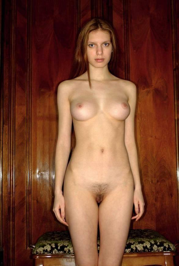Стройная молодая жена позирует без одежды