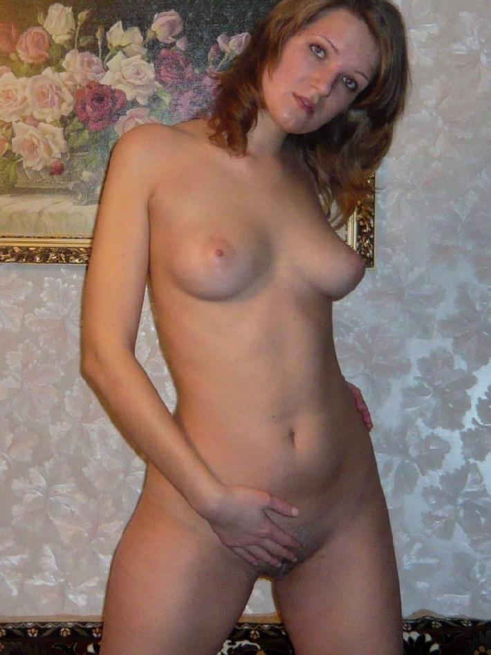 Красивая жена с аппетитной грудью позирует на фоне картины