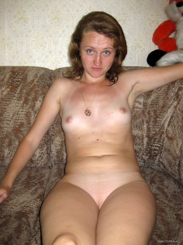 Удивленная голая жена без одежды сидит на диване