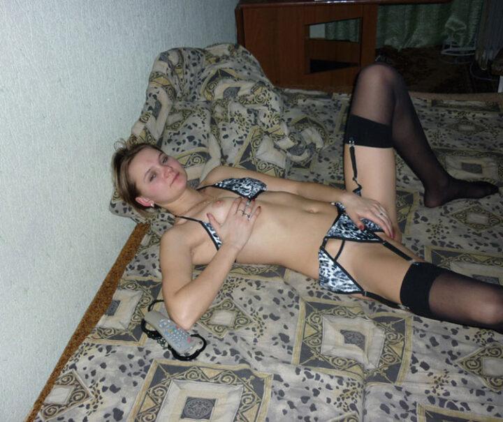 Молодая развратница в сексуальном белье с маленькой грудью лежит и удовлетворяет сама себя