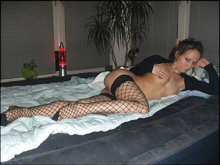 Развратная сексуальная женщина в сетчатых чулках и с голой грудью лежит на матрасе