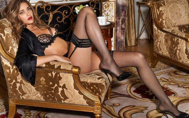 Сексуальная развратная длинноногая жена сидит в кресле