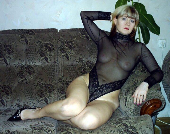 Роковая жена сидит на диване в прозрачном боди и в туфлях
