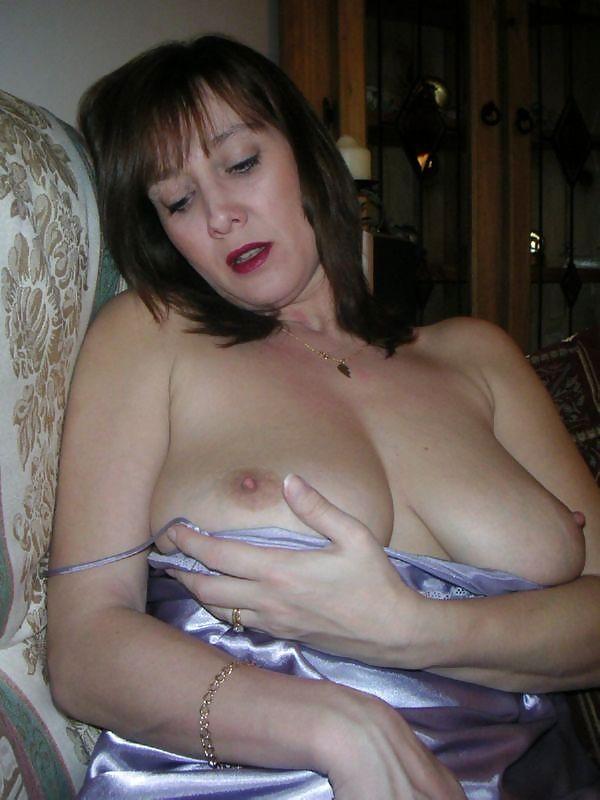 Зрелая жена сидит и смотрит на свою большую грудь