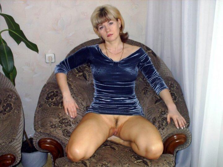 Женщина в синем бархатном платье сидит на корточках в кресле без трусов