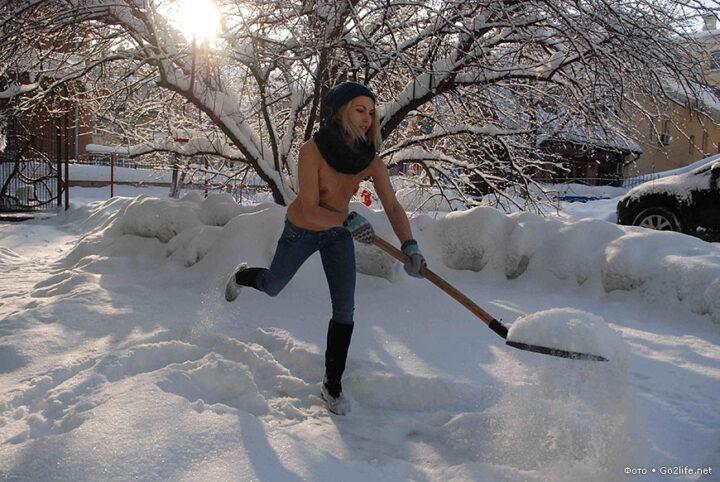 Девушка с голыми сиськами расчищает снег на даче.