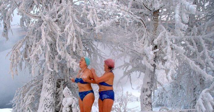 Две подружки в купальниках встречают утро Нового года в лесу