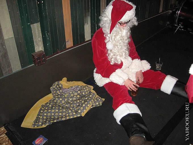 Печальный и пьяный Санта уснул на полу сидя.