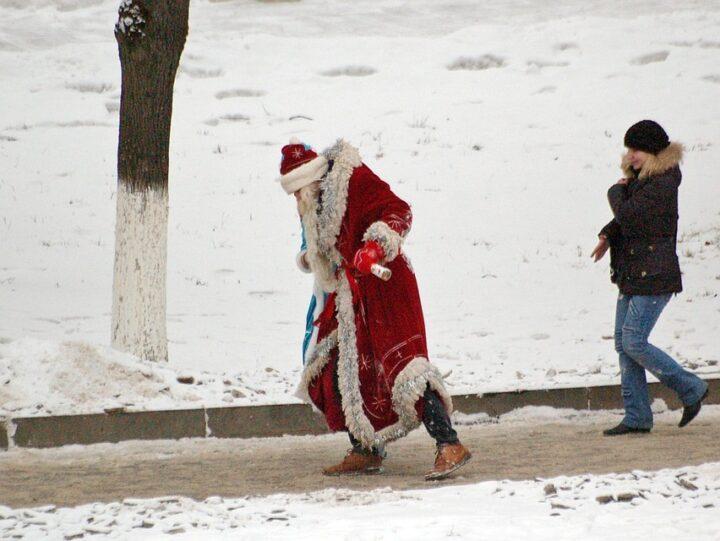 Пьяный Дед Мороз еле идет по улице.