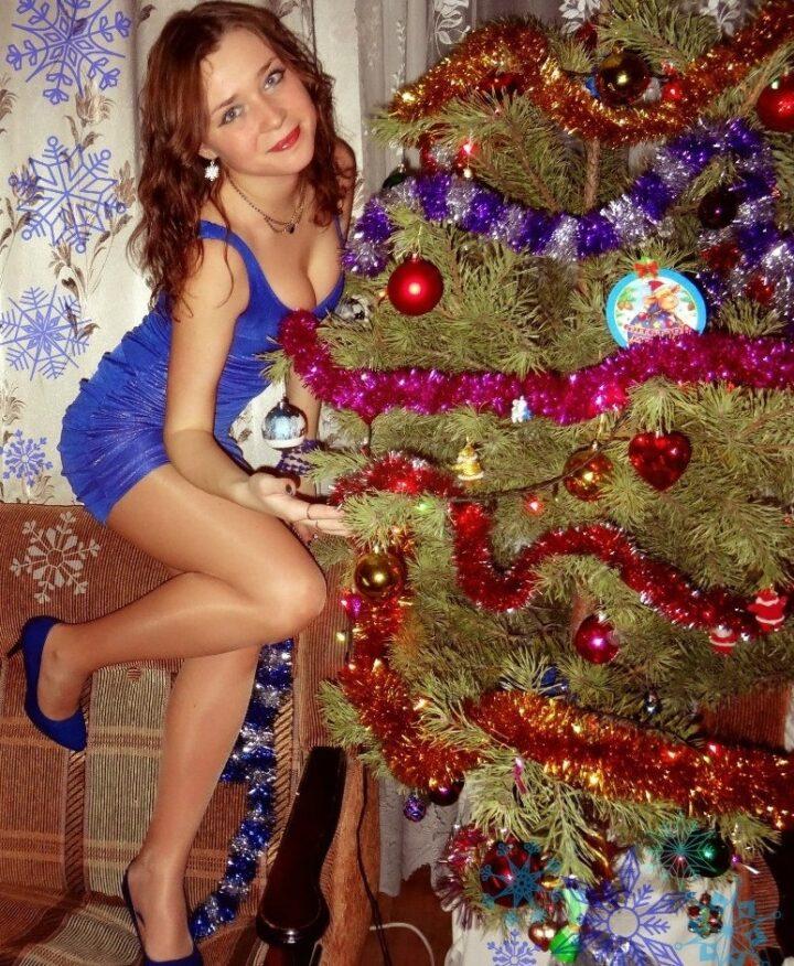 Милая девушка в мини синем платье залезла на диван в туфлях и позирует рядом с елкой.