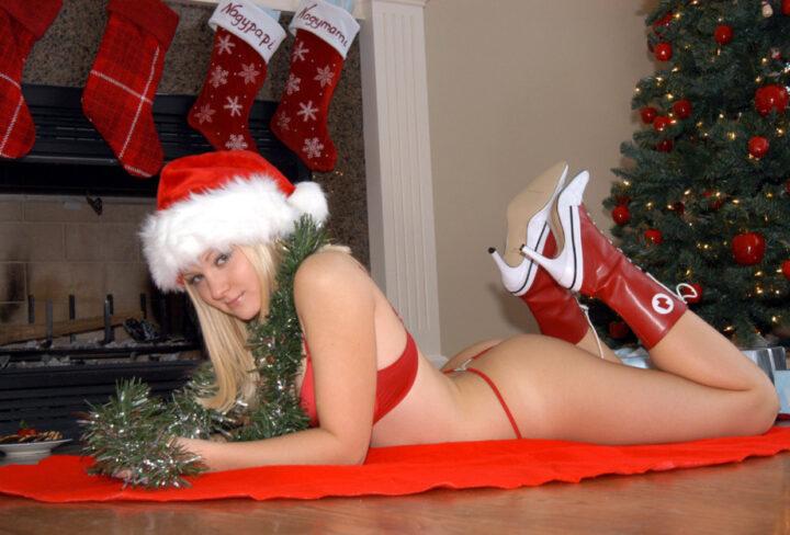 Соблазнительная снегурочка в красных стрингах лежит под елкой.