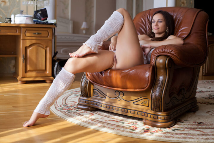 Женщина в гетрах сидит в кресле без одежды подняв ногу вверх.