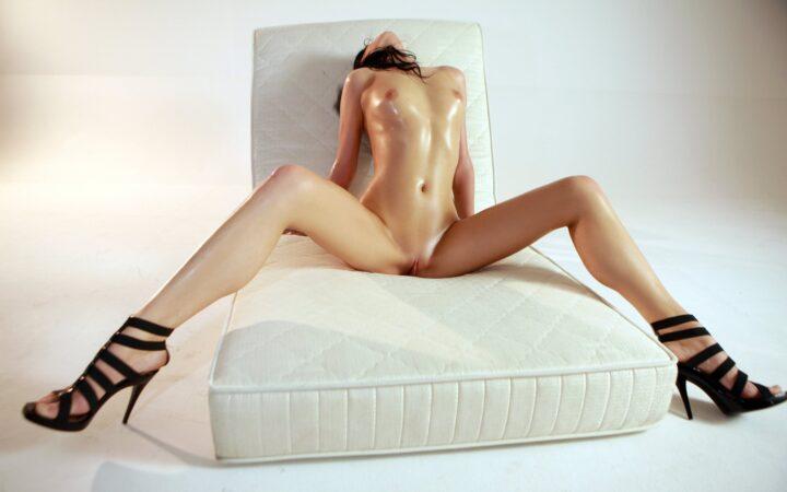 Девушка с красивой стройной фигурой сидит на матрасе широко расставив свои длинные ноги нак каблуках.