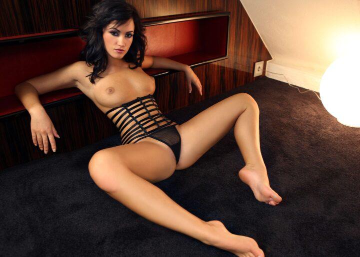 Развратная девушка сидит на полу с голыми сиськами в трусах раскинув ноги.
