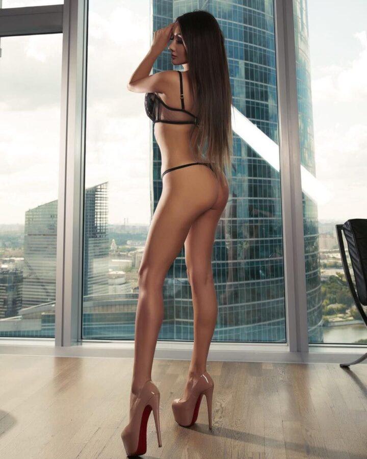 Красивая девушка с длинными волосами и длинными ногами стоит у окна.