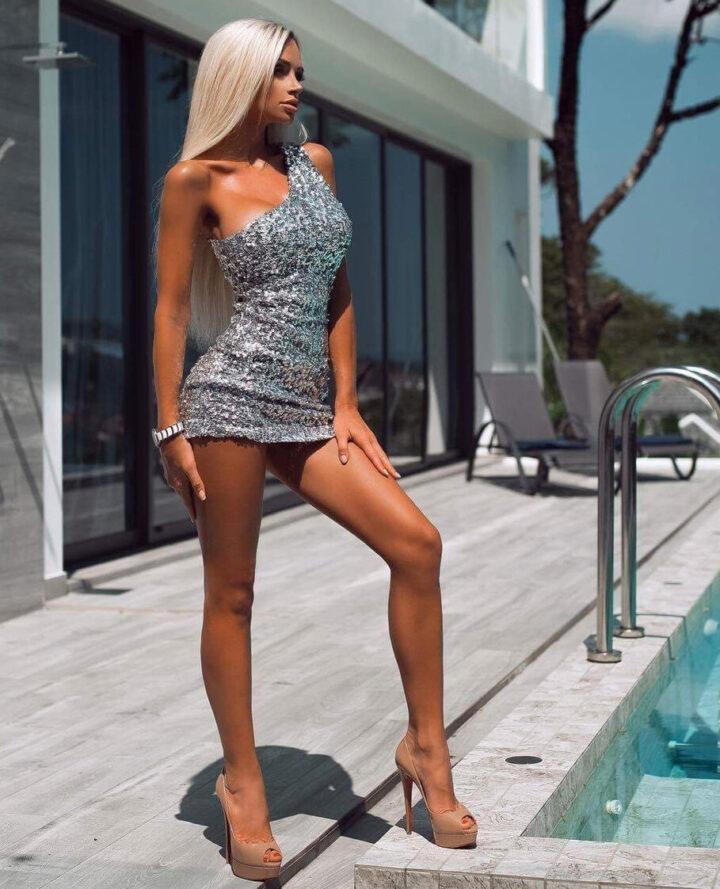 Шикарная девушка в блестящем платье с длинными ногами стоит у бассейна.