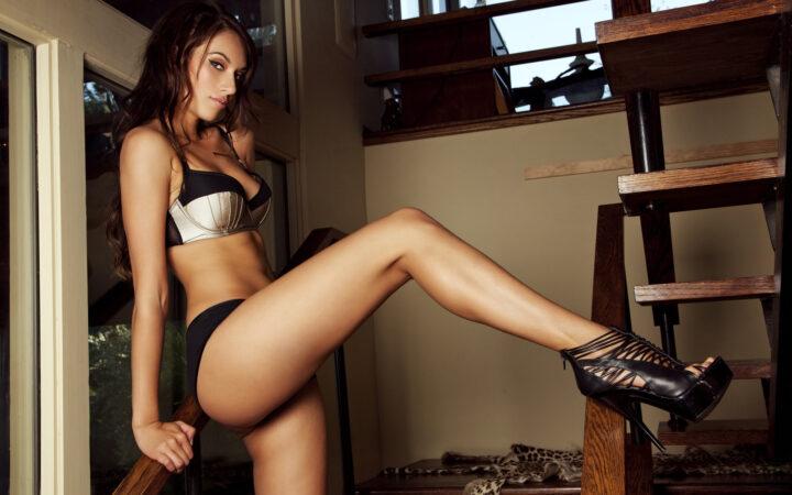 Брюнетка с большими сиськами задрала длинную ногу на перилу.