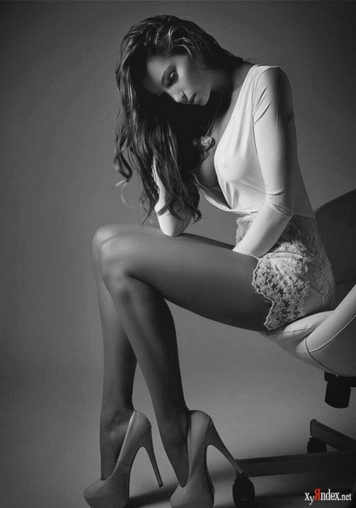 Задумчивая девушка стройная с длинными ногами сиди на краю кресла.