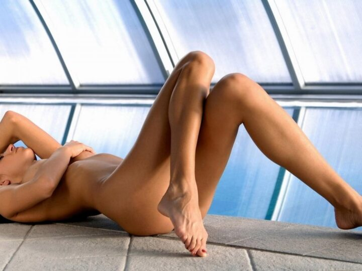 Стройная девушка с длинными ногами лежит на полу и закрывает рукой грудь.