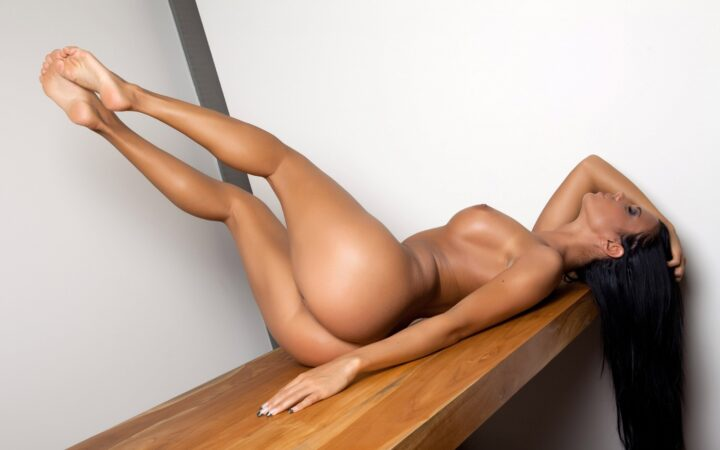 Длинноволосая красотка обнаженная лежит на скамейке с стройными красивыми ногами.
