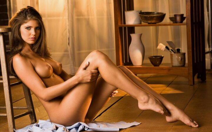Молодая красивая девушка без одежды сидит на полу облокотившись на стул.