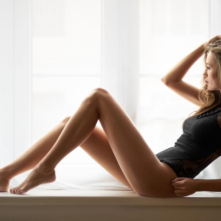 Девушка в кружевном боди с красивыми стройными ножками.
