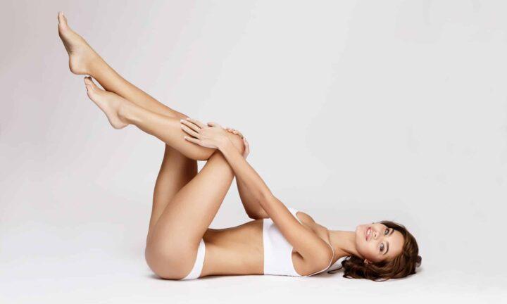 Прекрасная девушка лежит на полу и подняла вверх свои длинные ноги.