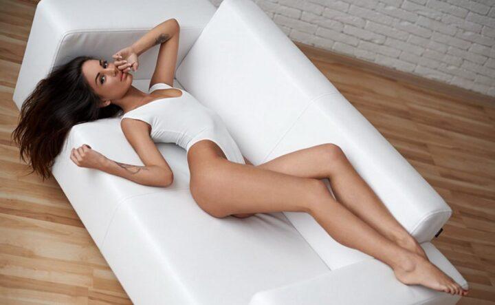 Сексуальная красивая девушка с длинными ногами в белом боди лежит на белом диване.