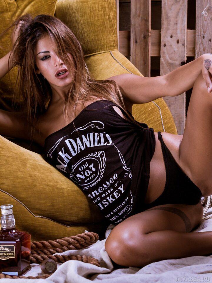 Сексуальная красотка в черных трусиках сидит в кресле.