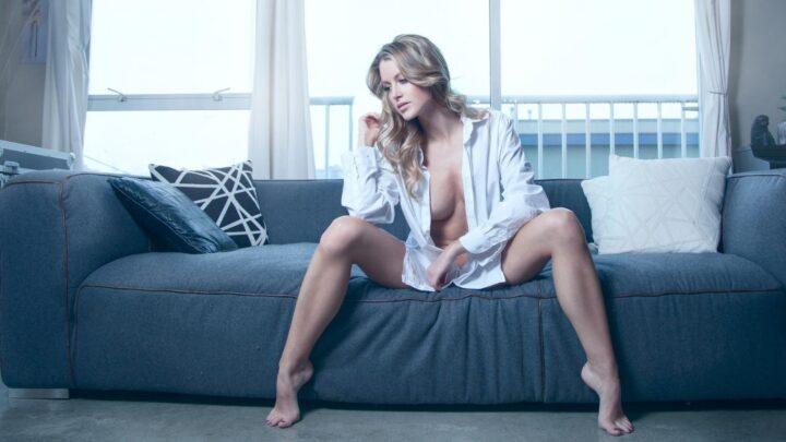 Блондинка в рубашке на голое тело сидит на диване широко поставив ноги.