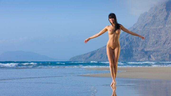 Красивая стройная девушка с ровными стройными ногами гуляет по берегу моря.