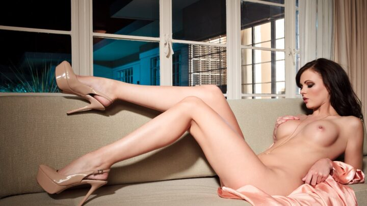 Брюнетка голая с красивыми ногами лежит на диване и гладит свою грудь.