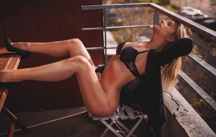 Красивая девушка в лифчике без трусов закинула ноги на столик.