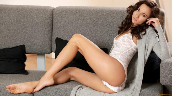 Нежная красивая девушка с стройными красивыми ножками сидит на диванчике.