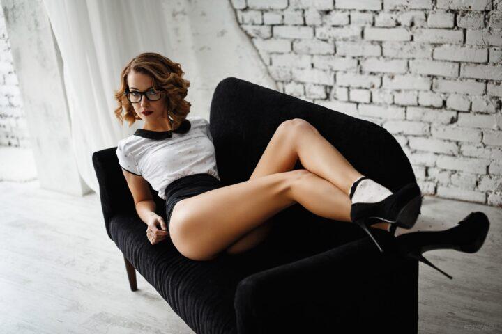 Сексуальная секретарша в очках с длинными ножками лежит на диванчике.