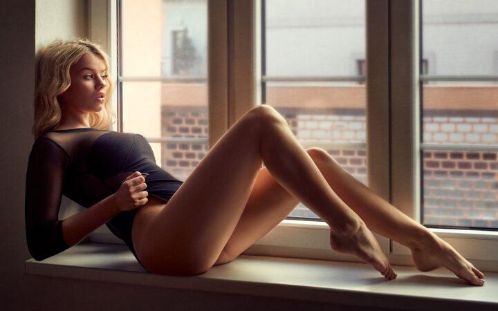 Задумчивая красотка с длинными красивыми ногами сидит на подоконнике.