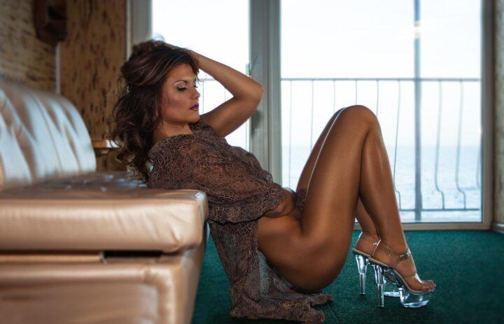 Женщина в платье на голое тело сиди на корточках на полу в прозрачных босоножках.